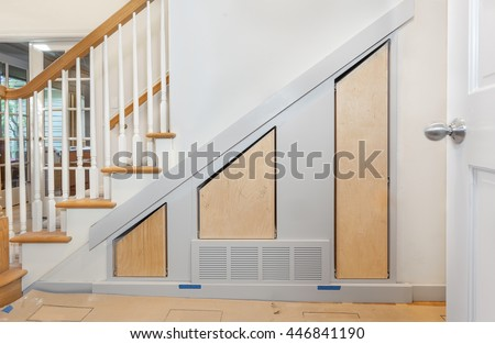 Custom built pullout cabinets on glides in slots under stairs - stock photo