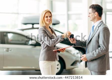 Customer buying a vehicle at car dealership - stock photo