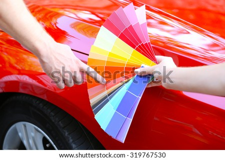 Customer choosing color over red car background - stock photo