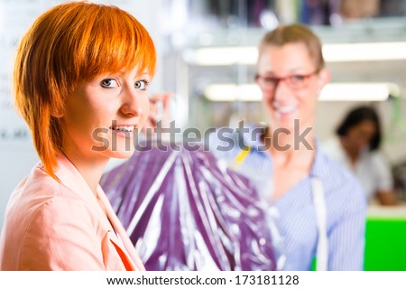 Customer collecting clothes in laundry shop or textile dry-cleaning packed in bag with hanger - stock photo