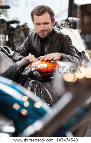 Customer examining motorcycle. Cheerful young men in leather clothing examining motorcycle before buying - stock photo