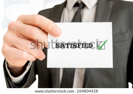 Customer feedback - Satisfied - concept with a businessman holding up a card with a ticked check box from a survey or feedback report and the word Satisfied, close up of his hand. - stock photo