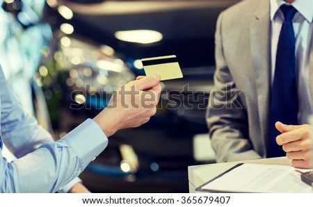 customer giving credit card to car dealer in salon