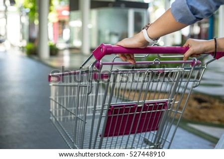 Customer holding Trolley for shopping in supermarket.