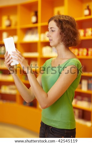 Customer in pharmacy reading information on medicine