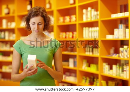 Customer in pharmacy reading information on medicine - stock photo