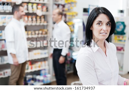 Customer in the pharmacy. In the background we can see another customer speaking with a  pharmacist