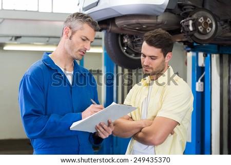 Customer listening to his mechanic at the repair garage - stock photo