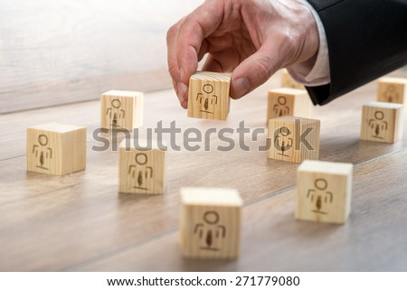 Customer-Managed Relationship Concept - Businessman Arranging Small Wooden Blocks with Symbols on the Table. - stock photo
