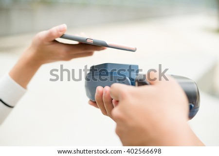 Customer pay with cellphone with NFC technology - stock photo