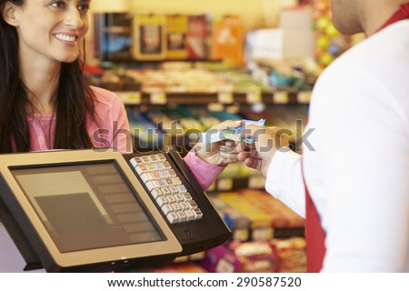 Customer Paying For Shopping At Checkout With Card - stock photo