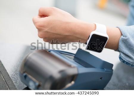 Customer paying through smart watch - stock photo