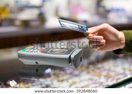 Customer paying with NFC technology by credit card - stock photo