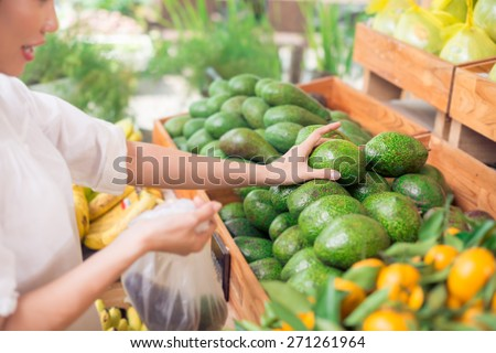 Customer picking up avocadoes at the grocery store - stock photo