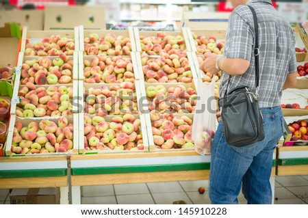 Customer select flat peaches in supermarket - stock photo