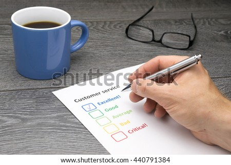 Customer service center offering excellent service. Customer filling out survey form while having a coffee - stock photo