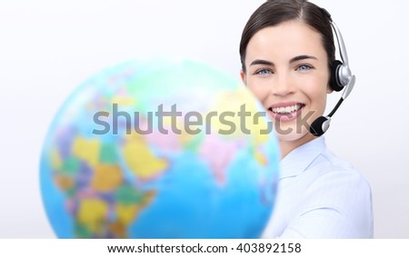 Customer service operator woman with headset smiling, holding globe, contact us concept - stock photo