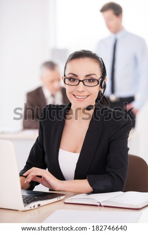 Customer service representative at work. Attractive young woman in formalwear adjusting her headset and smiling while people working on background - stock photo