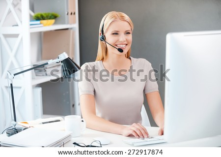 Customer service representative at work. Beautiful young woman in headset working at the computer and smiling while sitting at her working place in office - stock photo