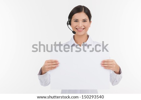 Customer service representative. Beautiful young female customer service representative in headset holding poster and looking at camera while isolated on white - stock photo