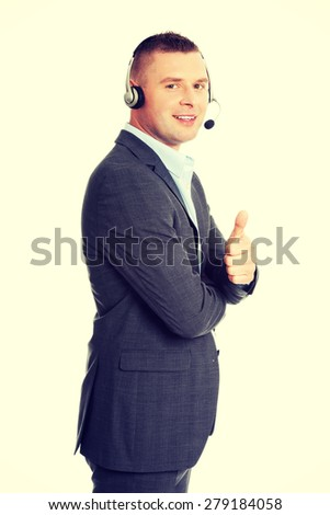 Customer service representative wearing a headset and gesturing thumbs up - stock photo