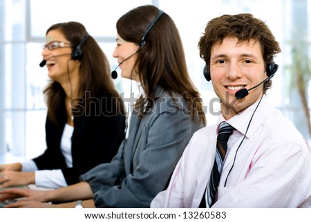Customer service team working in headsets, smiling. Man in front. - stock photo