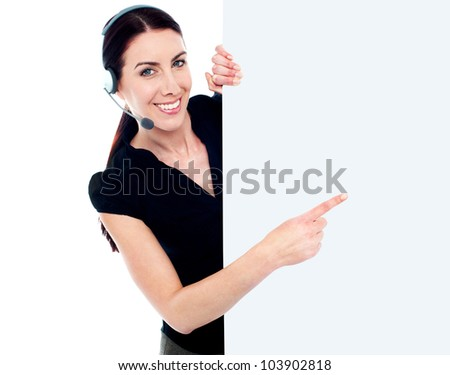 Customer service woman with headset showing and pointing at blank billboard sign banner - stock photo