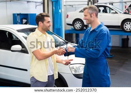 Customer shaking hands with mechanic taking keys at the repair garage - stock photo