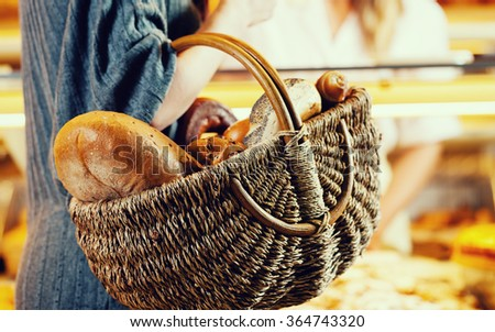 Customer shopping bread in baker carrying basket, filtered image - stock photo