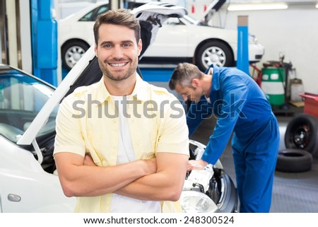 Customer smiling at the camera at the repair garage - stock photo