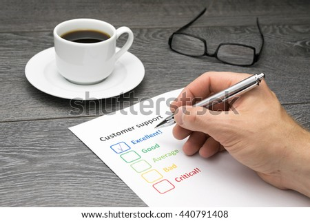 Customer support center offering excellent service. Customer filling out survey form while having a coffee - stock photo