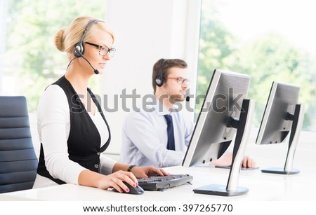 Customer support operators in formalwear working in call center office using computers. Business concept. - stock photo