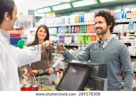 Customer using a credit card to pay in a supermarket - stock photo