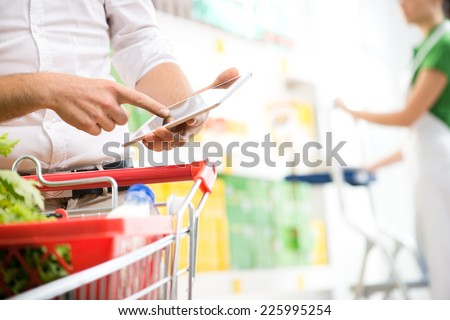 Customer using a digital tablet at supermarket with sales clerk on background. - stock photo