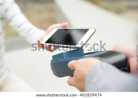 Customer using mobile phone to pay - stock photo