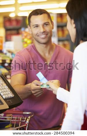 Customer Using Vouchers At Supermarket Checkout - stock photo