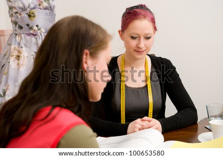 Customer with sales woman in clothing shop - stock photo