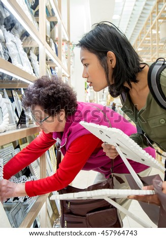Customers in the store choose frame for photo. Senior Caucasian woman with a young Asian woman shopping in supermarket.Multi-ethnic consumers are buying goods.Tourists are selected in souvenir shop.