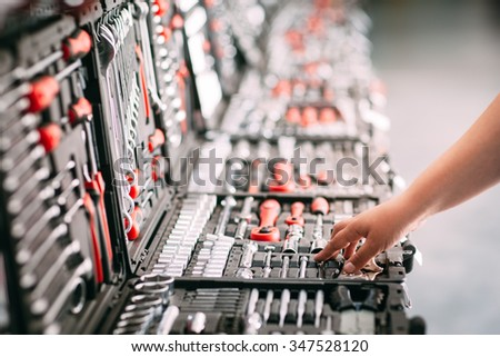 Customers or worker (builder, repairman, handyman) at the store chooses wrench instrument (tools). Display of tools shop marketing for home and auto repair - stock photo