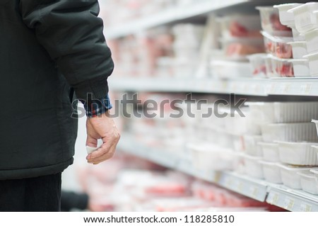 Customers selecting beef and pork slices on shelves in supermarket - stock photo