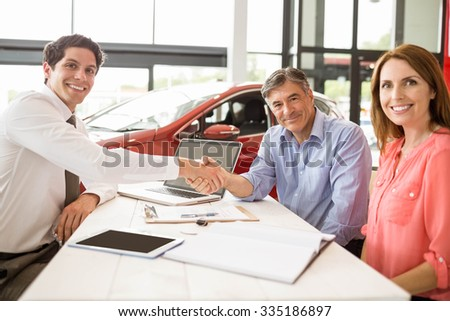 Customers signing some important documents at new car showroom