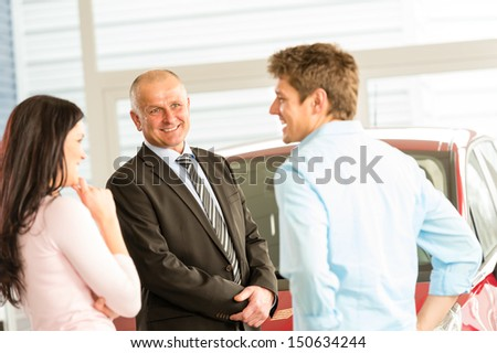 Customers talking with car agent in showroom - stock photo