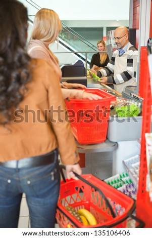 Customers with shopping baskets standing in line at checkout counter in supermarket