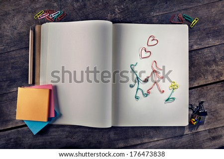 Customizable love messages using two lovers made from paper clips, blank vintage notebook, blank post-its on wooden background. - stock photo