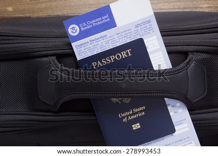 Customs declaration and passport lie on the road suitcase, passing visa control.