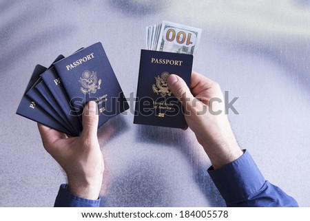 Customs official taking a bribe as he holds a batch of five United States passports in his hand for a group or family traveling together with 100 dollar bills in one to grease his palm, overhead view - stock photo