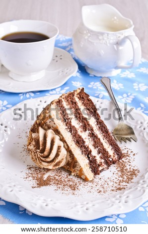 Cut a piece of cake brown with cream on the plate
