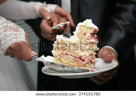 cut a piece of wedding cake in the hands of the bride and groom