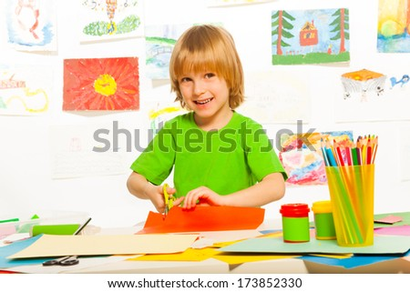 Cut and glue lesson with 4 years old blond boy with scissors and smile - stock photo