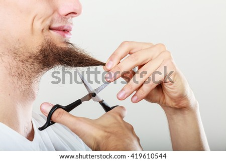 Cut and shave concept. Young man with long beard holding scissors. Part face boy cutting hair on chin. - stock photo